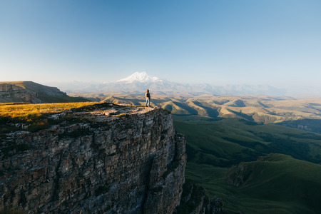 Traveler standing on top of Bermamyt plateau and looking on Elbrus mountain. Karachay-Cherkessia, Caucasus, Russia. Stock Photo