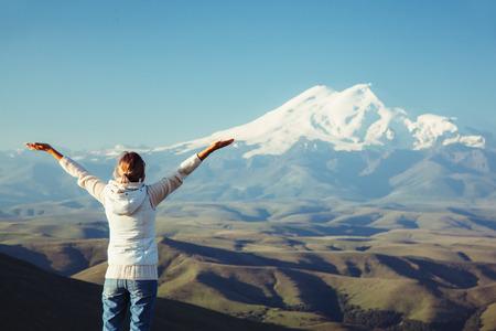 elbrus: Traveler standing on top of Bermamyt plateau and looking on Elbrus mountain. Karachay-Cherkessia, Caucasus, Russia. Stock Photo