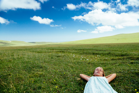 Tween girl relaxing on green grass in spring field, blue skies, idyllic scene Stock Photo