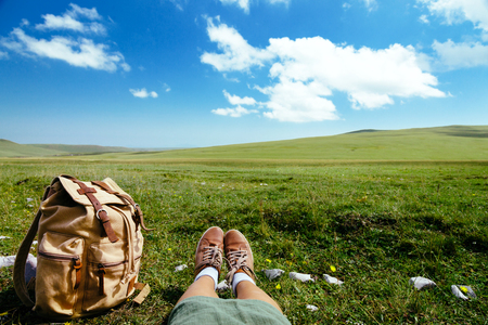 foots: Travel backpack and travelers foots on green grass in spring field, blue sky and clouds, idyllic scene