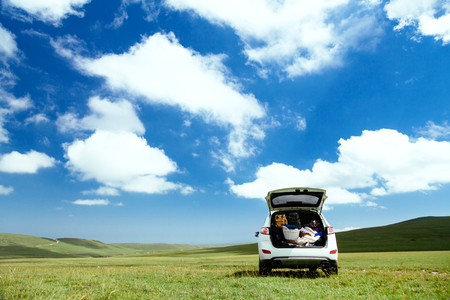 car trunk: Car with full trunk of backpacks in the field on green grass and blue skies Stock Photo