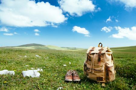 旅行のバックパックや靴のスプリング フィールド、青空と雲、牧歌的な風景の緑の草の上