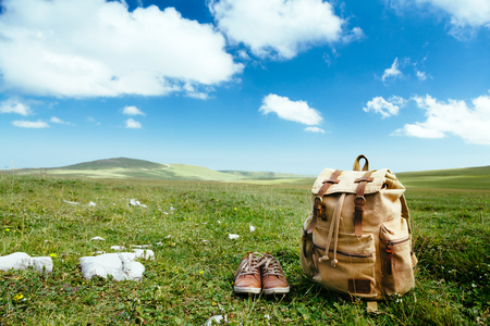 Travel backpack and shoes on green grass in spring field, blue sky and clouds, idyllic scene