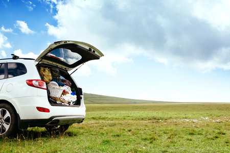 Car with full trunk of backpacks in the field on green grass and blue skies Stock Photo