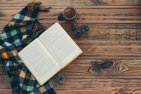 Mok met theezakje, boek en plaid winter deken op vintage houten tafel, bovenaanzicht