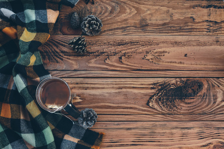 checkered scarf: Mug with tea bag and plaid winter scarf on old brown wooden table, top view