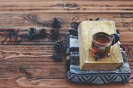 winter wood: Cup with tea bag, sweater, book and pine cones on old brown wooden table