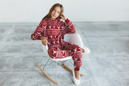 10 years old child dressed in warm Christmas pajamas sitting on modern rocking chair in concrete scandinavian interior. Lazy winter morning, comfortable scene. Stock Photo