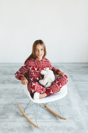 10 year old: 10 years old child dressed in warm Christmas pajamas sitting on modern rocking chair in concrete scandinavian interior. Lazy winter morning, comfortable scene. Stock Photo