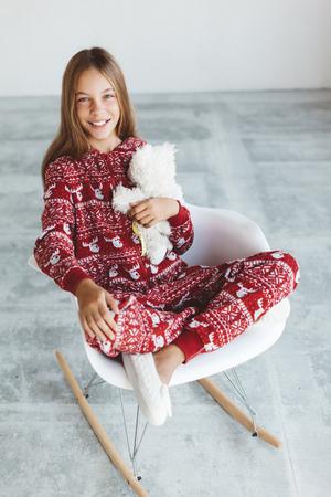 10 years old child dressed in warm Christmas pajamas sitting on modern rocking chair in concrete scandinavian interior. Lazy winter morning, comfortable scene. 版權商用圖片