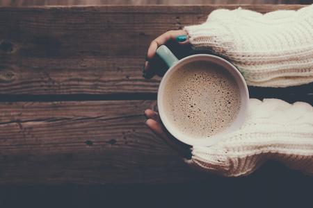Vrouw met kop warme koffie op rustieke houten tafel, close-up foto van de handen in warme trui met mok, winterochtend concept, bovenaanzicht