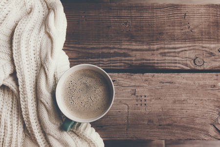 Cup of hot coffee on rustic wooden table, closeup photo warm sweater with mug, winter morning concept, top view