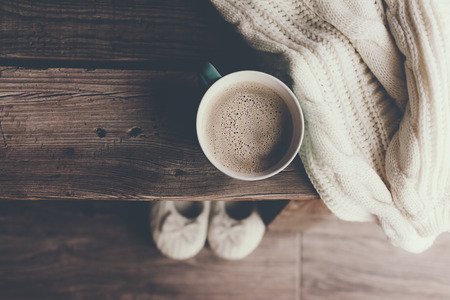 Cup of hot coffee on rustic wooden bench, closeup photo of warm sweater with mug and slippers, winter morning concept, top view Stock Photo