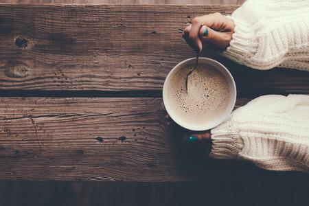 Mujer que sostiene una taza de café caliente en la mesa de madera rústica, foto del primer de las manos en el suéter caliente con la taza, el concepto de la mañana de invierno, vista desde arriba