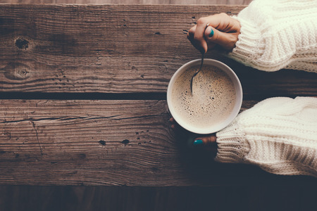 Woman holding cup of hot coffee on rustic wooden table, closeup photo of hands in warm sweater with mug, winter morning concept, top view Stockfoto