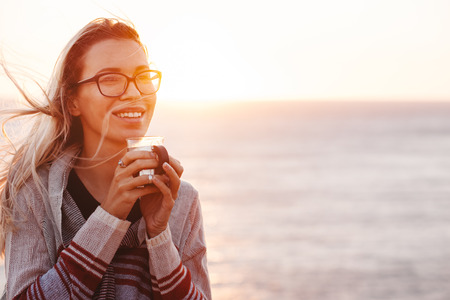 Woman wearing sweater smiling and drinking hot tea outdoors in autumn sunlight. Fall cozy concept, backlit.