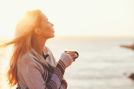 sol radiante: La mujer llevaba suéter beber té caliente al aire libre en la luz del sol de otoño. Otoño concepto acogedor, con retroiluminación. Foto de archivo
