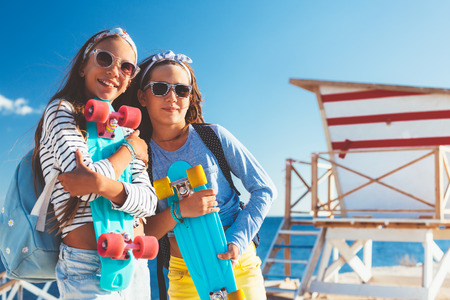 skateboarder: Two 10 years old children wearing cool clothing posing with colorful skateboards on the beach, urban style, pre teen summer fashion. Stock Photo