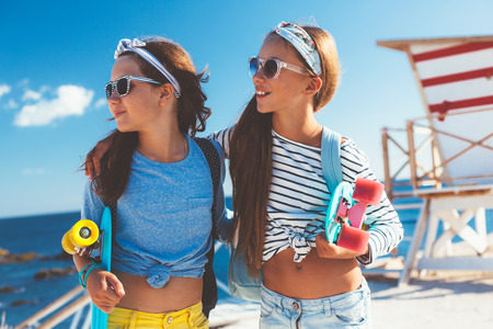 Two 10 years old children wearing cool clothing posing with colorful skateboards on the beach, urban style, pre teen summer fashion. Stock Photo