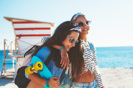 pre teen: Two 10 years old children wearing cool clothing posing with colorful skateboards on the beach in sunlight, urban style, pre teen summer fashion. Stock Photo