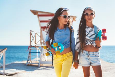 해변에서 햇빛, 도시 스타일, 사전 하이 틴 여름 패션에서 화려한 스케이트 보드와 함께 포즈 멋진 의류를 입고 두 10 살짜리 아이. 스톡 콘텐츠