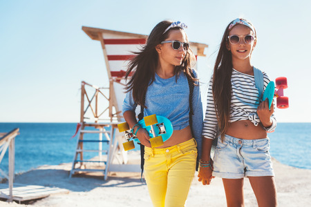 Two 10 years old children wearing cool clothing posing with colorful skateboards on the beach in sunlight, urban style, pre teen summer fashion. Stock Photo