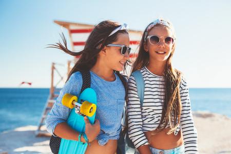 Twee 10 jaar oude kinderen dragen van koele kleding poseren met kleurrijke skateboards op het strand in het zonlicht, stedelijke stijl, pre tiener zomer mode.