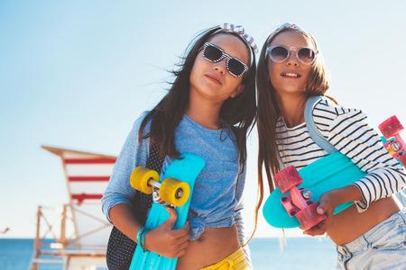 Deux vieux 10 années des enfants portant fraîche posant des vêtements avec des planches à roulettes colorées sur la plage, style urbain, la mode ado d'été pré.