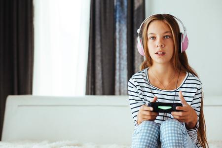 10 ans pré fille adolescente tenant console de jeu et de jouer sur un sofa à la maison le matin