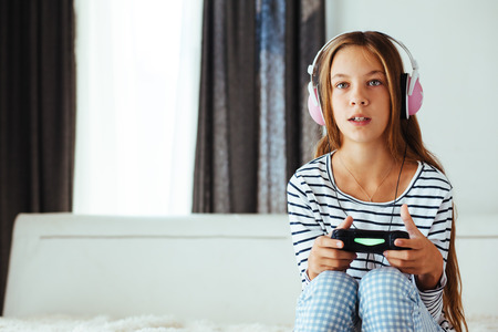 pre teen: 10 years old pre teen girl holding gaming console and playing on a sofa at home in the morning