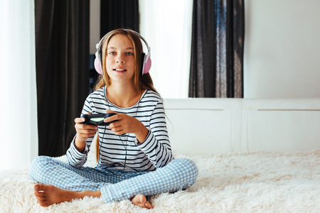 pre teens: 10 years old pre teen girl holding gaming console and playing on a sofa at home in the morning