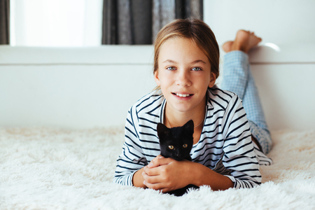 pre teen girl: 10 years old pre teen girl lying down on sofa and playing with black kitten