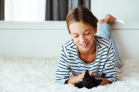 pre teen: 10 years old pre teen girl lying down on sofa and playing with black kitten