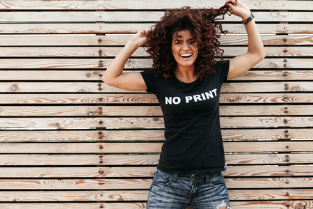 Hipster girl with curly hair wearing t-shirt and jeans posing against wooden wall, swag street style