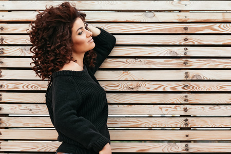 black sweater: Beautiful girl with curly hair wearing black sweater posing against wooden wall, profile view Stock Photo