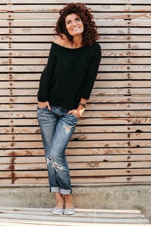 검은 스웨터와 청바지 나무 벽에 포즈와 웃 고, 전체 길이 입고 곱슬 머리를 가진 아름 다운 친절 한 소녀 스톡 콘텐츠