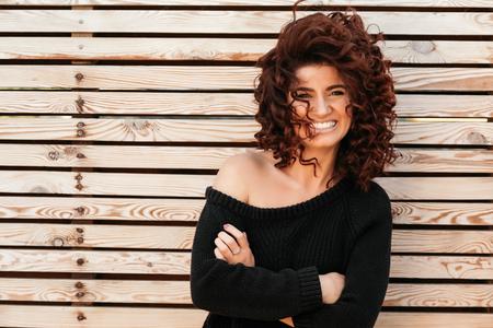 cabello negro: chica amable hermosa con el pelo rizado, llevaba suéter negro posando contra la pared de madera y sonriendo