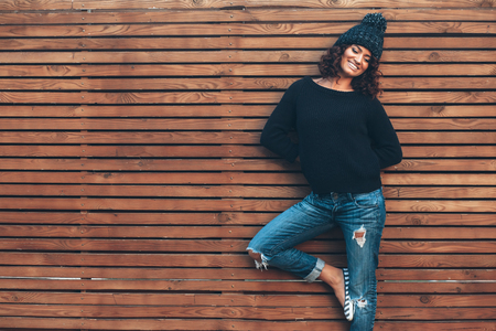 street style: Hipster girl with curly hair wearing black sweater, hat and jeans posing against wooden wall, swag street style, autumn outfit