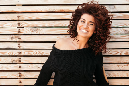 people laughing: Beautiful friendly girl with curly hair wearing black sweater posing against wooden wall and smiling