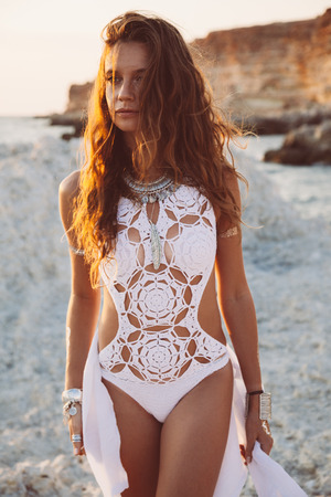 monokini: Beautiful boho styled girl wearing white crochet swimsuit with flash tattoo at the beach in sunlight