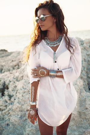 iluminado a contraluz: Hermosa chica de estilo boho con camisa blanca con la joyería étnica de la moda y del flash del tatuaje en la playa en la luz del sol Foto de archivo