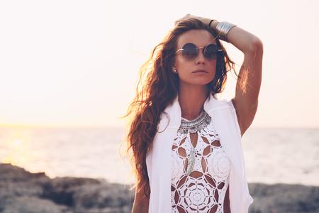 自由奔放に生きる美しいスタイルの日光の下でビーチでフラッシュ ・ タトゥーのかぎ針編みの白水着を着ている少女