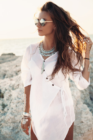 Beautiful boho styled girl wearing white shirt with fashion ethnic jewelery and flash tattoo at the beach in sunlight