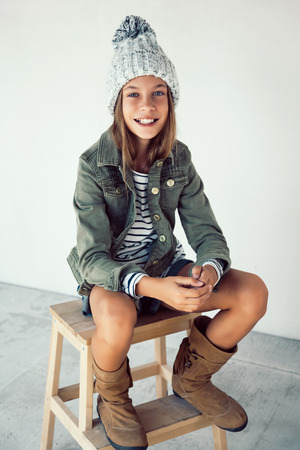 Fashion pre teen girl of 10 years old wearing fall clothing and boots, hipster style Stock Photo