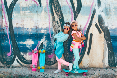 Two 7 years old children wearing cool fashion clothing posing with colorful skateboard against graffiti wall, urban style Stock Photo