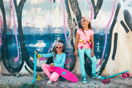 Twee 7 jaar oude kinderen dragen van koele mode kleding poseren met kleurrijke skateboard tegen graffiti muur, stedelijke stijl