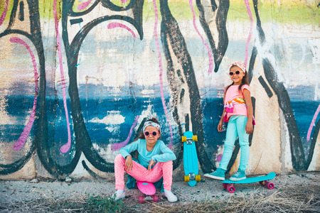 child model: Two 7 years old children wearing cool fashion clothing posing with colorful skateboard against graffiti wall, urban style Stock Photo