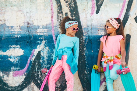 fashion clothing: Two 7 years old children wearing cool fashion clothing posing with colorful skateboard against graffiti wall, urban style Stock Photo