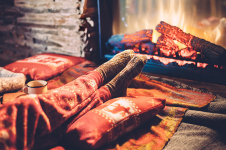 blanket: Cold fall or winter evening. People resting by the fire with blanket and tea. Closeup photo of feet in woolen socks. Cozy scene. Stock Photo