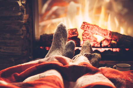 Cold fall or winter evening. People resting by the fire with blanket and tea. Closeup photo of feet in woolen socks. Cozy scene. Stock Photo
